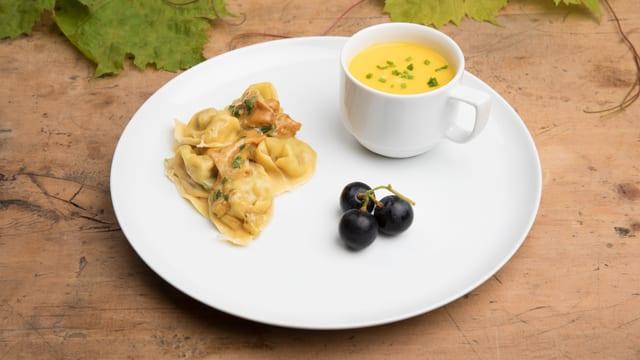 Vorspeisenteller mit Tortellini und Suppe.