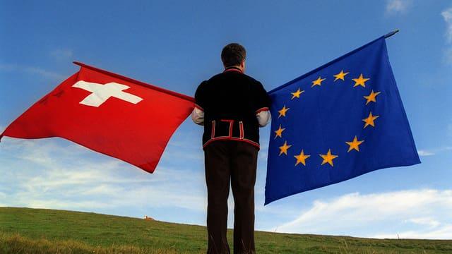 Eine Person hält eine Schweizer und eine EU-Flagge.