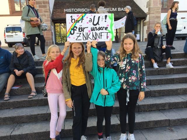 Vier Mädchen halten ein Transparent in die Höhe.