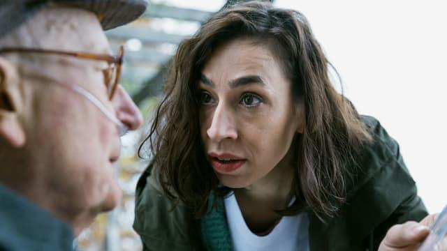 Eine junge Frau im Gespräch mit einem alten Mann.