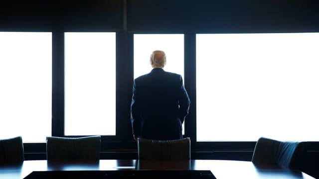 Trump blickt aus einem Gebäude heraus, mit dem Rücken zur Kamera.