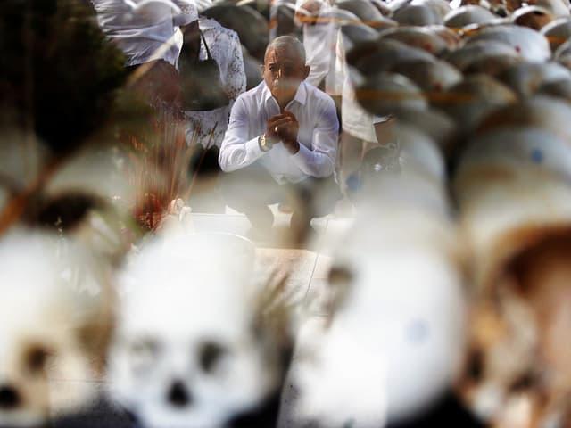 Trauernder sitzt hinter aufgereihten Schädeln, am «Tag des Zorns»