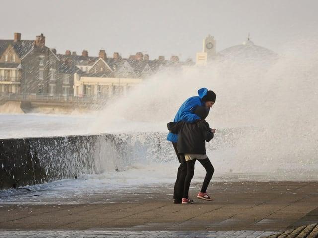 Uferpromenade mit Gischt und Wellen. Menschen können kaum laufen.