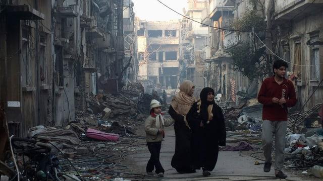 Ein Mann, zwei Frauen und ein Kind gehen eine von Schutt gesäumte Strasse entlang.