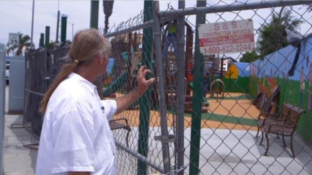 Eini Mann steht vor einem Gitter, hinter dem sich ein Spielplatz befindet.