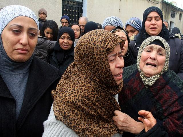 Frauen mit Kopftüchern, weinend und klagend.