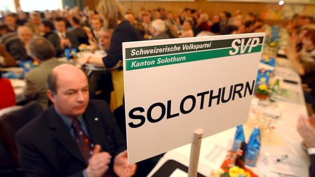 Viele Leute an einer Parteiversammlung, auf eine Tisch steht ein Schild, darauf steht SVP Solothurn