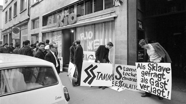 eine schwarz-weiss Fotografie von Demonstrierenden mit Plakaten