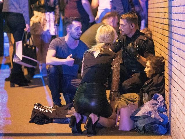 Menschen sitzen geschoockt am Boden.