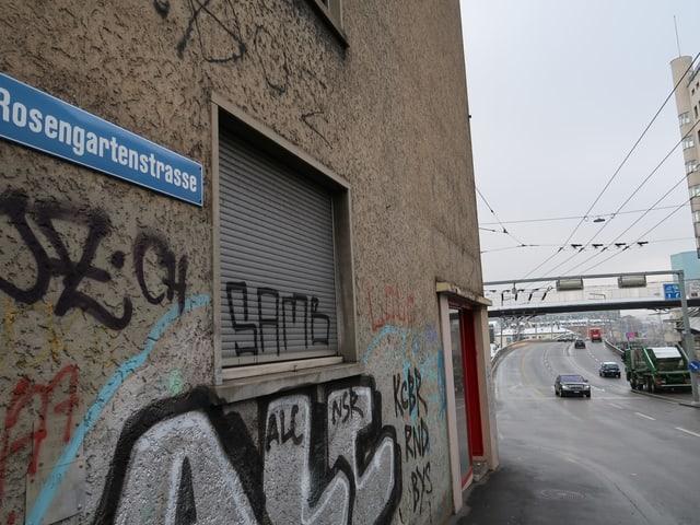 Strassenschild an Haus mit Graffiti