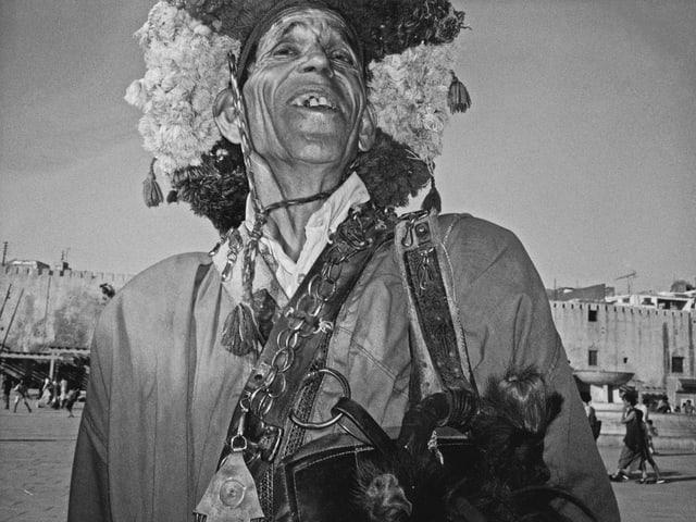 Schwarz-Weiss-Foto: Ein Mann mit einem breitkrempigen Hut aus Stoffquasten aus der Froschperspektive fotografiert.