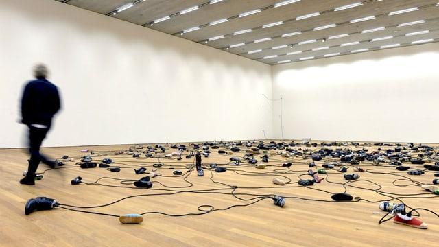 Kabel am Boden, die in Schuhen stecken.