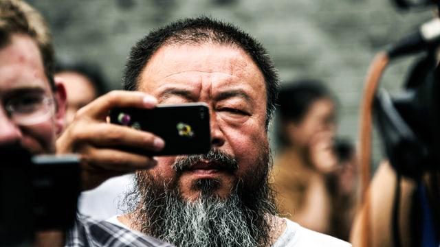 Ai Wei Wei steht in einer Menschenmenge und hält ein Smartphone vor seinem Gesicht.