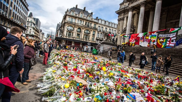 Blumenmeer in der Brüsseler Innenstadt, Menschen trauern am Rand.