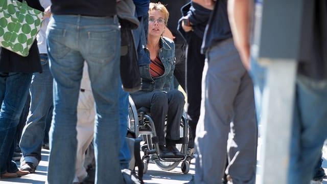 Rollstuhlfahrerin in einer Menschenmenge
