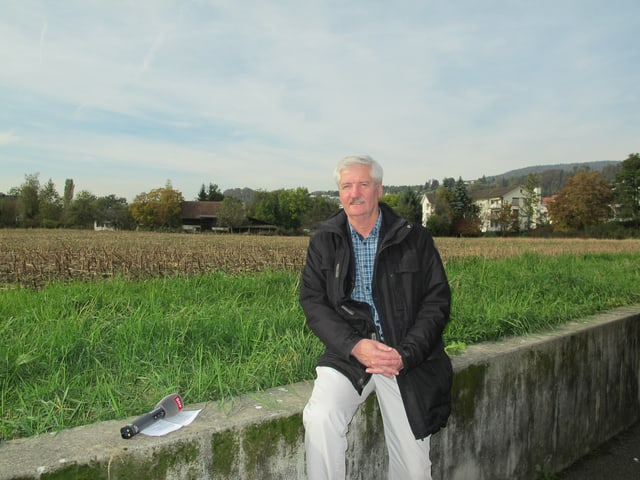 Ein Mann mit grauen Haaren und Schnurrbart sitzt auf einer Mauer vor einer Wiese.