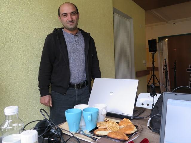 Mann mit Tablett, auf dem Kuchenstücke und Tassen stehen