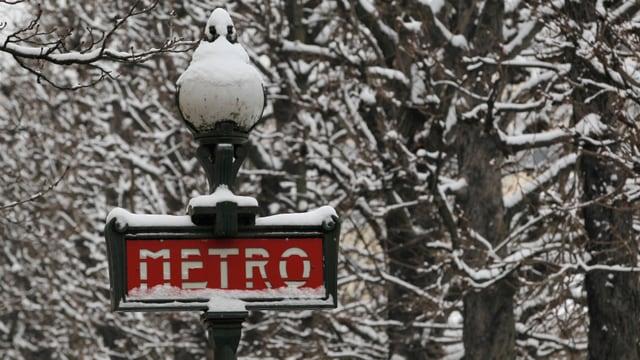"""Ein Schild mit der Bezeichnung """"Métro"""" an einer Haltestelle der Pariser Untergrundbahn, umgeben von schneebedeckten Bäumen."""