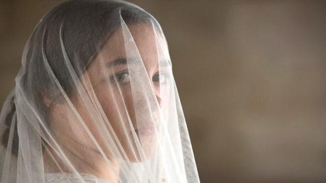 Eine Frau mit einem Schleier vor dem Gesicht.