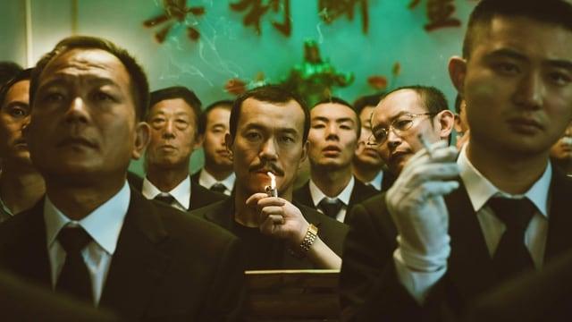 Eine Gruppe Männer blickt in die Kamera. In der Mitte zündet sich einer eine Zigarette an.