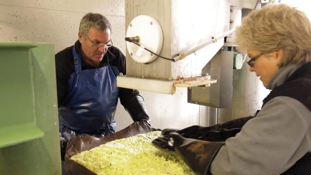 Urs und Heidi Kocher verteilen Apfelstücke auf einem Blech.