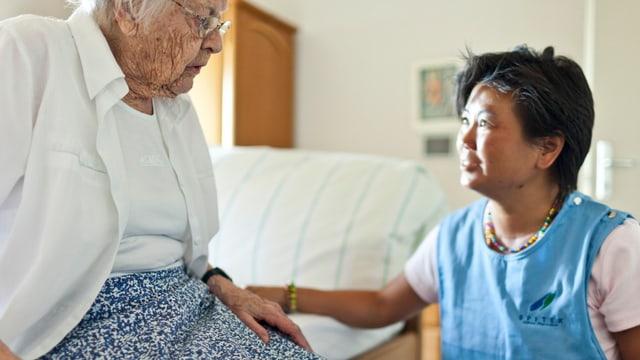 Eine Altersheimbewohnerin wird von einer Pflegefachfrau betreut.