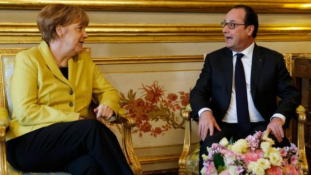 Merkel und Hollande sitzen nebeneinander