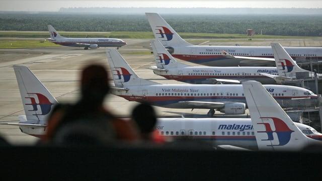 Zwei Menschen im Flughafen Kuala Lumpur betrachten Maschinen der Airline. (reuters)