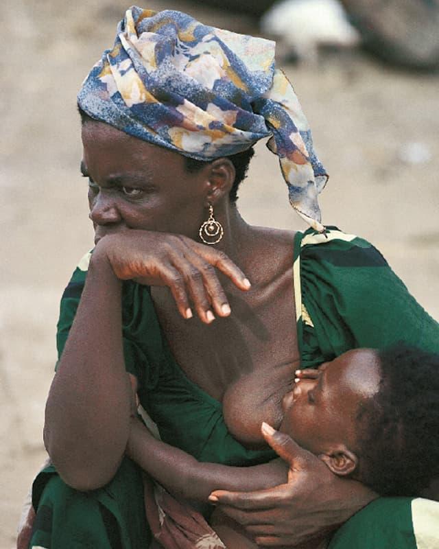 Eine dunkelhäutige Frau mit einem bunten Kopftuch stillt ihr kleines Kind.