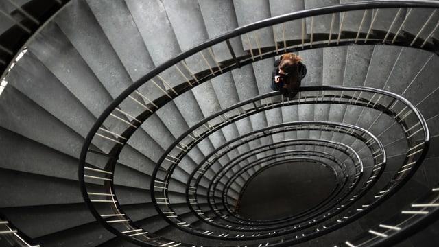 Frau läuft auf einer Wendeltreppe