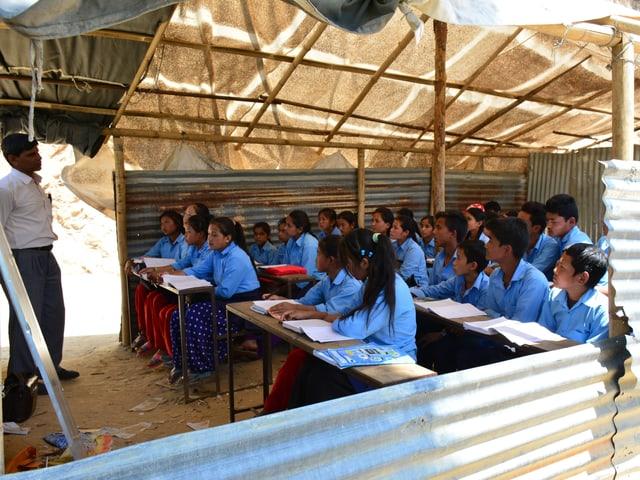 Schüler und Lehrer in Wellblechhütte mit Tuch-Dach.