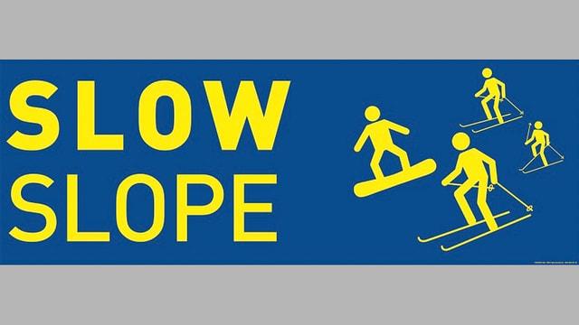 Schild mit Aufschirft Slow Slope und Piktorgrammen von Skifahrern.