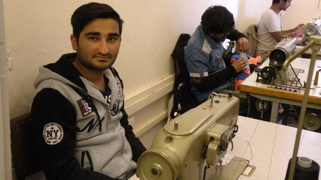 Ein junger Mann sitzt an einer Nähmaschine.