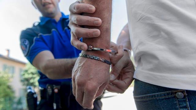 Polizist führt Mann in Handschellen ab.