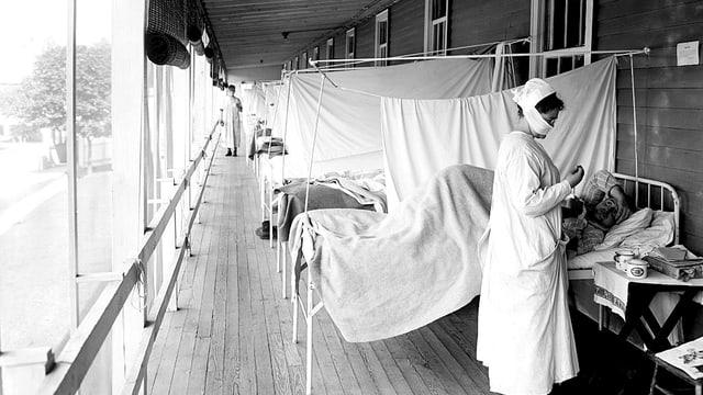 Eine in weiss gekleidete Frau steht an einem Krankenbett