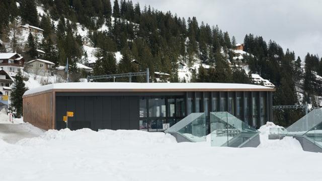 Haus mit hohen Glasfenstern im Winter mit Schnee.
