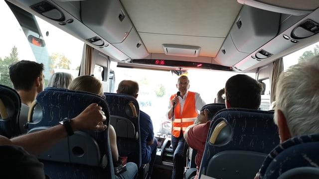 Mann in oranger Warnweste spricht in einem Bus in ein Mikrofon.