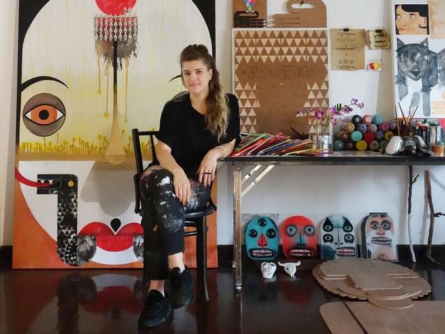 Die Künslterin Maja Hürst sitzt vor verschiedenen an die Wand gelehnten Werken, auch auf dem Boden ist eine flache Figur aus Holz hingelegt.