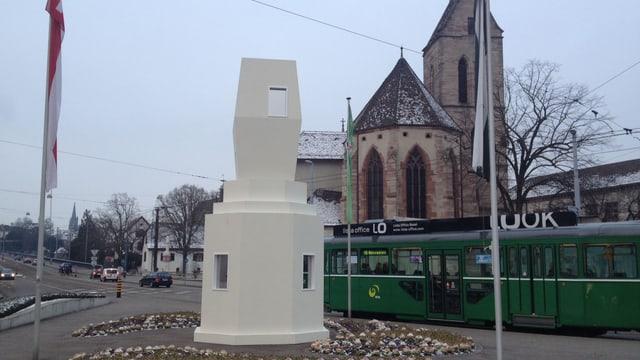 Ein weisses turm-ähnliches Gebilde auf dem Wettsteinplatz mit Tram und Theodorskirche im Hintergrund.