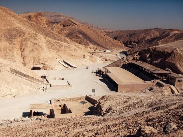 Blick von oben in das Tal der Könige, braune Hügel und einige Gebäude