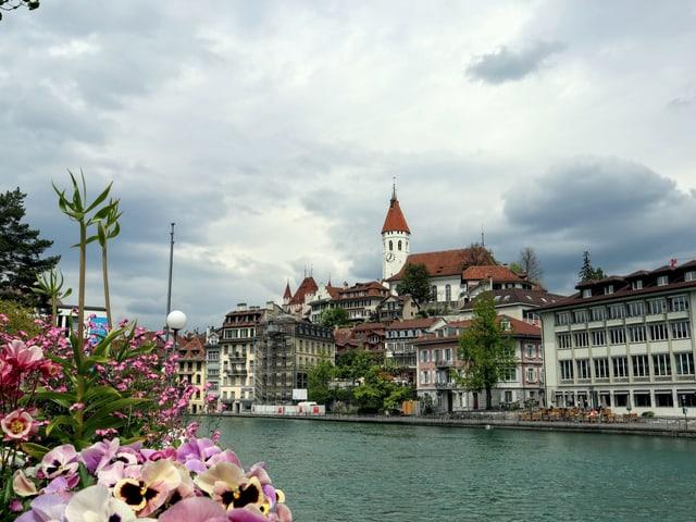 Im Vordergrund der See, dahinter die Stadt Thun, am Himmel viele Regenwolken