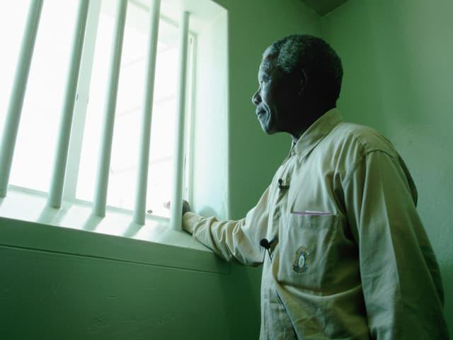 Nelson Mandela steht am Fenster seiner Gefängniszelle, in der er 27 Jahre lang gelebt hatte. Besuch auf Robben Island 1994.