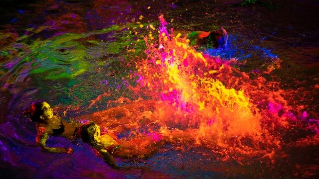Schwimmende Personen in einem bunt beleuchteten Wasserbecken.