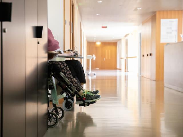 Rollstuhl kommt aus Tür in einen Gang