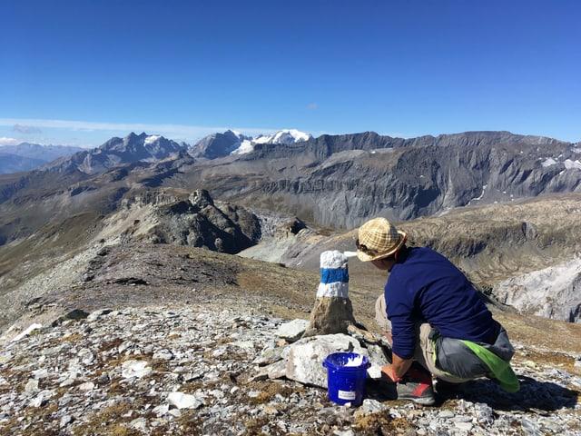 Frau kniet am Boden und malt Fels blau-weiss an