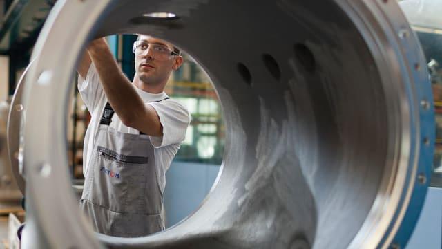 Arbeiter durch ein Metallrohr fotografiert, an dem er etwas montiert