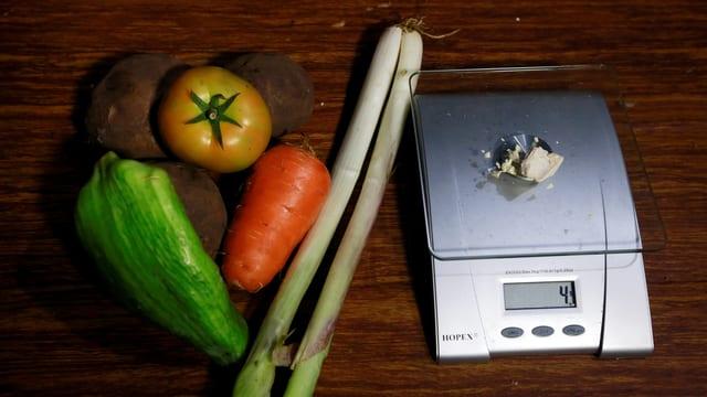 Eine Peperoni, eine dicke Karotte, eine Tomate, zwei Lauchstangen und drei grosse Kartoffeln neben einer Waage mit Cocapaste.