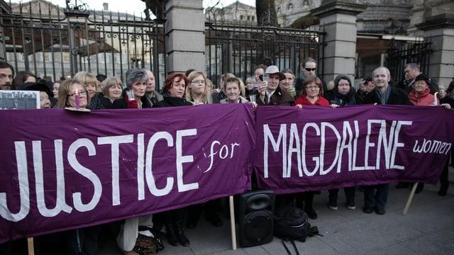 """Frauen halten vor dem Regierungsgebäude in Dublin ein Transparent """"Justice for Magdalene Women"""" in die Höhe"""