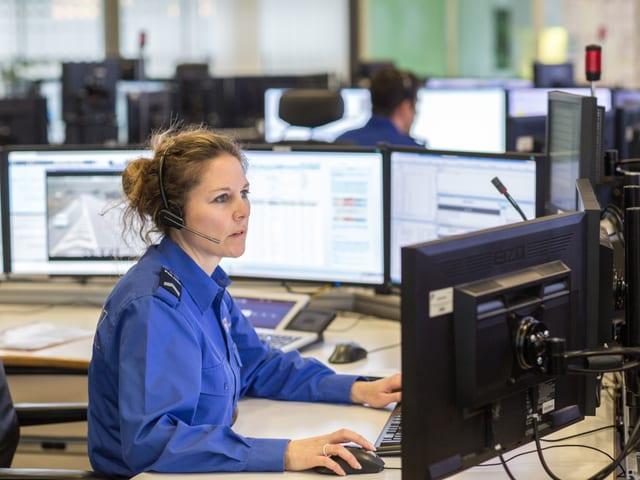 Frau in Polizeiuniform sitzt vor mehreren Bildschirmen und telefoniert.