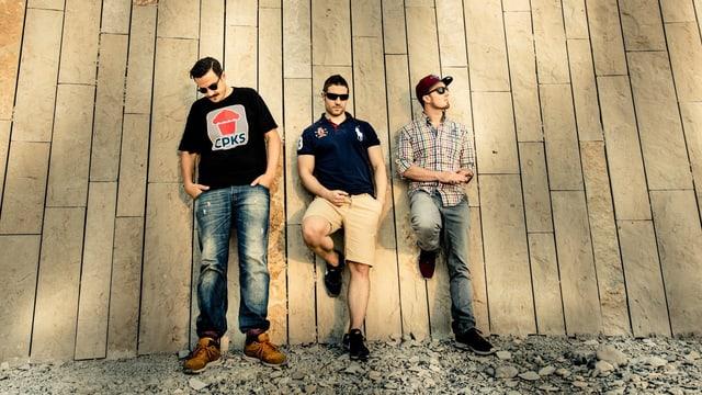 drei männer lehnen an eine holzwand